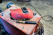 pic of welding  - Red welding helmet with wire clamp instrument - JPG