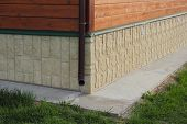 foto of downspouts  - Wooden house corner with plastic draipipe photo - JPG