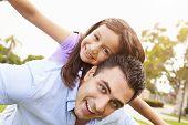 pic of piggyback ride  - Father Giving Daughter Piggyback Ride In Garden - JPG