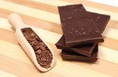 foto of chocolate spoon  - Grated chocolate on wooden spoon and stack of dark chocolate chocolate pieces - JPG