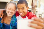 stock photo of pre-adolescents  - Teenage Couple Sitting On Bench In Mall Taking Selfie - JPG