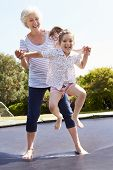 stock photo of bouncing  - Grandmother And Granddaughter Bouncing On Trampoline - JPG
