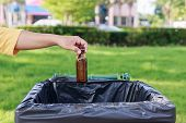picture of throw up  - Close up hand throwing empty glass bottle into the trash - JPG