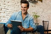 foto of internet-cafe  - Casual Man Using Tablet Computer Smile Sitting in Cafe Surfing Internet  - JPG