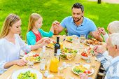 pic of pray  - Top view of family of five people holding hands and praying before dinner while sitting at the table outdoors - JPG