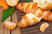 pic of continental food  - Fresh croissant and orange on wooden table horizontal - JPG