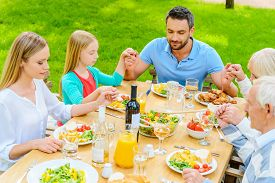 picture of pray  - Top view of family of five people holding hands and praying before dinner while sitting at the table outdoors - JPG