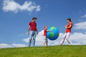 Boy gets on  hip  large inflatable ball, alongside stand mother with  father