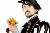 Portrait of a handsome man grandee in 16th century costume holding golden rose. Isolated over white