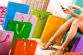 Image of woman dialling while shopping with colorful paperbags placed on the floor