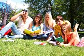 foto of young adult  - Portrait of smart friends reading books in park together - JPG