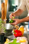 stock photo of chef knife  - Close up of chef in a commercial restaurant kitchen working - JPG
