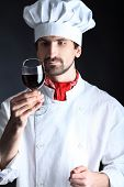 Portrait of a man cook holding a glass of red wine. Shot in a studio over black background.