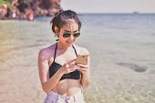 Swimsuit Concept. Beautiful Girl Wearing A Swimsuit Playing Mobile On The Beach. Beautiful Girl Is T poster