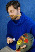 Artist in blue sweater adds oil paints on a palette. He holds bristles in his mouth.