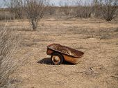 A child's wagon abandoned and left to rust in the Arizona desert.