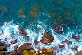 Top Aerial View Of Blue Waves Crashing On Rocky Australian Coastline. Summer Seascape With Ocean Wav poster