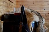 Closeup Of A Hunters Gun With Whiskey And An Animal Pelt. poster