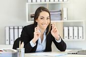 Hopeful Executive Crossing Fingers Looking At Camera At Office poster