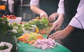Professional team cooks and chefs preparing meals at busy hotel or restaurant  kitchen poster