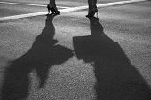 Two Modern Girls On High Heels Stand On Sunny Asphalt With Two Big Shadows. Black And White. Shadow  poster