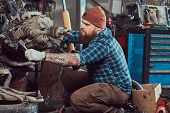 Brutal Tattooed Bearded Mechanic Specialist Repairs The Car Engine Which Is Raised On The Hydraulic  poster