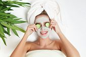 Portrait Of Beauty Woman Laying With Towel On The Head, Cucumber On Her Eyes, Facial Mask. Spa Thera poster