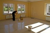 image of premises  - woman cleans new empty office premise with plastic windows with kind on city - JPG