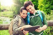 travel, hiking, backpacking, tourism and people concept - smiling couple with backpacks and tablet p poster