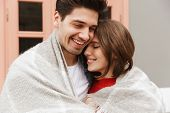 Portrait of beautiful couple in love smiling and hugging together outside cafe wrapping in one blank poster