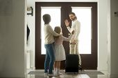 Smiling Father Waves Goodbye To Wife And Daughter Leaves Home For Business Trip Stands At Door With  poster