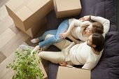 Relaxed Couple Resting On Sofa On Moving Day, Young Renters Relaxing On Couch Moved Into Apartment W poster