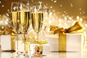 foto of special occasion  - Glasses of champagne with gold ribboned gifts - JPG