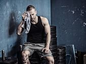 Muscular Young Bodybuilder Drying Sweat From His Face With A Towel After Workout In A Gym. Tattoo Re poster