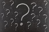 Signos de interrogación escritas en la pizarra. Problemas para resolver el concepto.