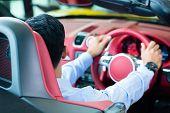 Asian man testing new sports car at car dealership poster
