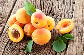 Ripe apricots and apricot leaves on the wooden background. poster