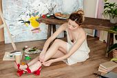 Beautiful Young Woman Wearing Red Sandals While Sitting On Floor In Art Studio poster
