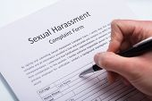 Close-up Of A Human Hand Filling Sexual Harassment Complaint Form With Pen poster