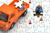 Miniature People Construction Worker On White Jigsaw. Using As Background Business Concept And Finan poster