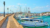 Perspective of pier with moored fishing boats in the port of Aegina town, Aegina Island, Greece poster
