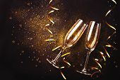 Celebration toast with champagne. Two champagne flutes with golden streamers on dark background poster