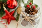 Pine Cone Or Conifer Cone And Christmas Red Holly Balls In Glass Bottle With Rustic Ribbon Bow Tie I poster