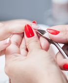 Nail salon - Cut cuticle on the female forefinger