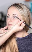 Retrato da bela jovem com esteticista fazendo maquiagem olhos sombra