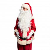 Middle age handsome man wearing Santa Claus costume and beard standing sticking tongue out happy wit poster