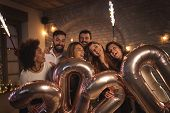 Group Of Young Friends Having Fun At New Years Eve Party, Holding Balloons Shaped As Numbers 2020 An poster