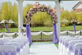 picture of wedding arch  - wedding arbor with a flower arch and white chairs - JPG