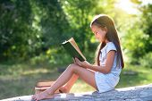 Charming little girl with long brown hair reads book outdoor sitting on tree in summer park or in a  poster