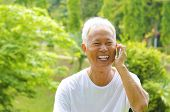 Healthy senior Asian man on the phone outdoor green park